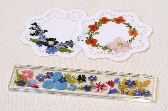 写真:押し花体験教室の作品例。白いレースのコースターと透明なアクリル定規
