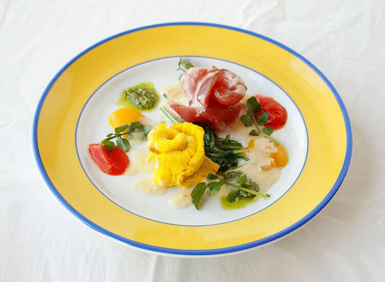 写真:マグロ刺身と卵をバラのように巻いたプレート。赤・黄・緑・白の鮮やかなソースが散りばめられている