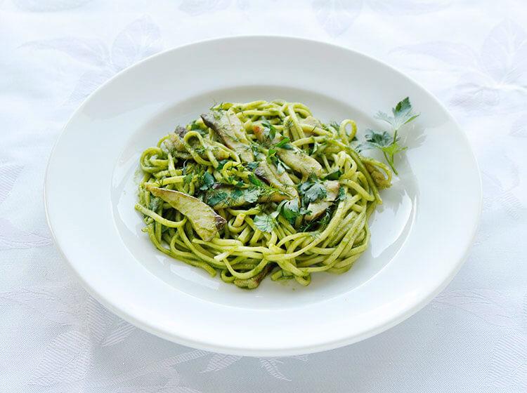 写真:よもぎの緑色が鮮やかなソースに鯵の切り身と中太パスタが和えられている