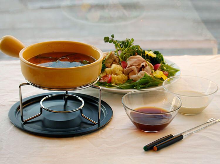 写真:オイルフォンデュの鍋の奥に豚肉と野菜がたっぷり盛られたプレート。手前に2種のソースが並んでいる