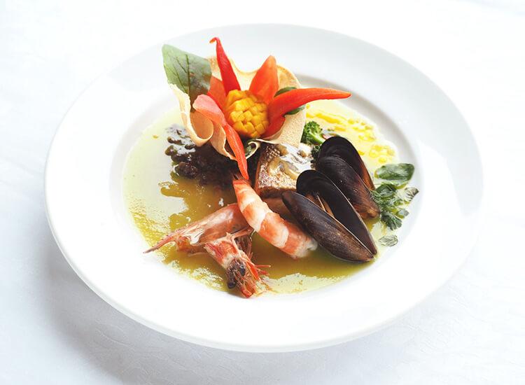 写真:野菜を花のようにあしらったブイヤベース。烏貝とエビなどの魚介がごろごろ入っている