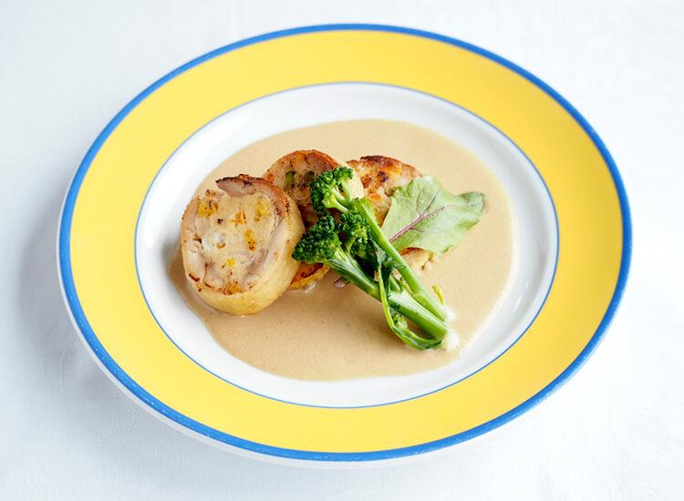 写真:クリーム状のソースの上に輪切りにした鶏肉とスティックブロッコリーが乗っている