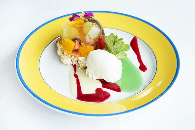 写真:フルーツがドーム状に固められたゼリーとバニラアイス。ベリーソースと青緑色のソースが添えられている