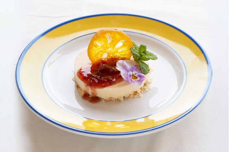 写真:ベリーソースがかかった円形のレアチーズケーキにドライの輪切りみかんが添えられている