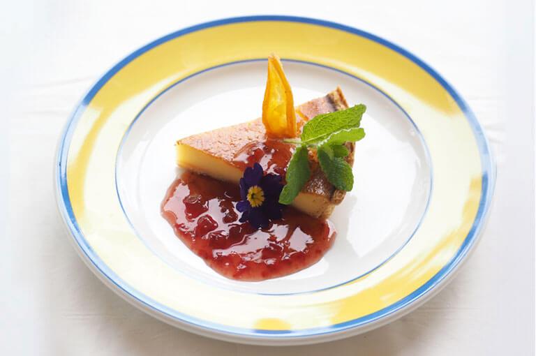 写真:三角形にカットされたチーズケーキに苺のソースがたっぷりかかっている。ミントとドライフルーツ、お花が添えられている