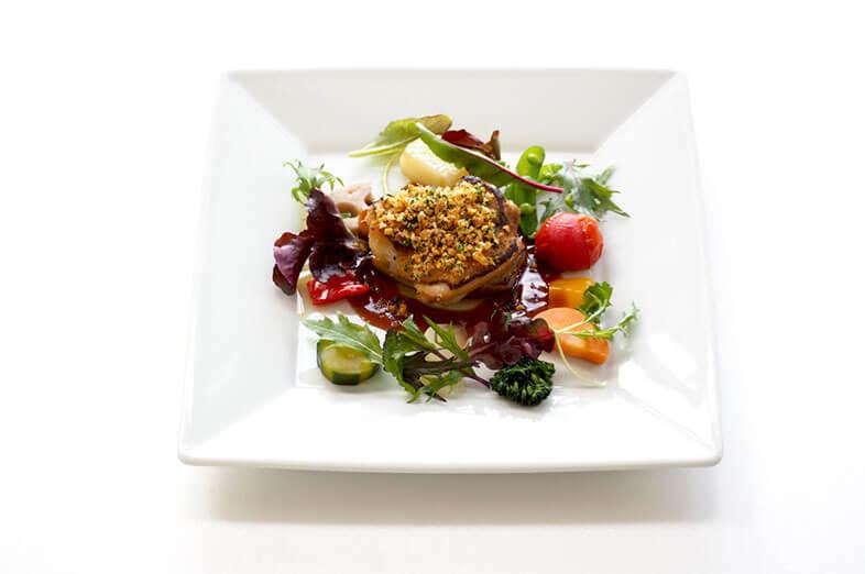 写真:香ばしそうなローストチキンに褐色のソースと野菜が添えられている