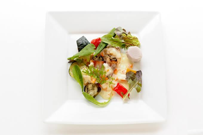 写真:クリームソースがかかった魚と牡蠣のベーコン巻。ベビーリーフなどの野菜が彩りを添えている