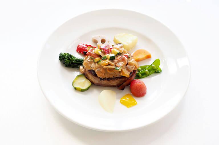 写真:側面にベーコンが巻きつけられたハンバーグに様々な野菜を和えたソースが乗っている。その周りに時計のようにカラフルな野菜が並んでいる