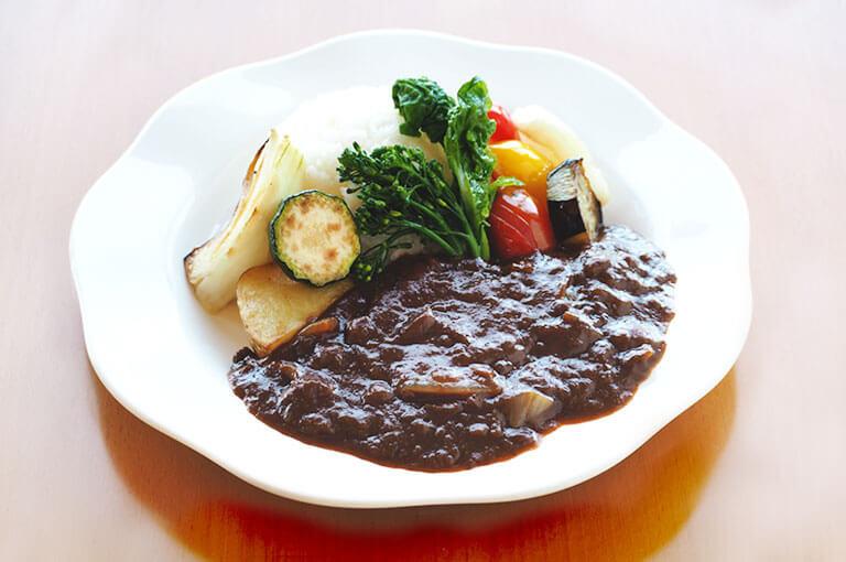 写真:ズッキーニやパプリカなどごろごろ野菜が添えられたハヤシライス