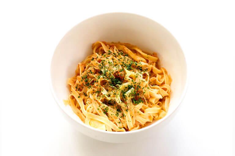 写真:平打ちパスタにキャベツとツナのトマトソースが絡んだパスタ