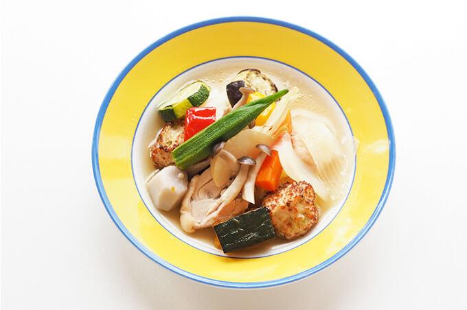写真:野菜と鶏肉がごろごろ入ったポトフが黄色とブルーの縁取りのお皿に盛られている
