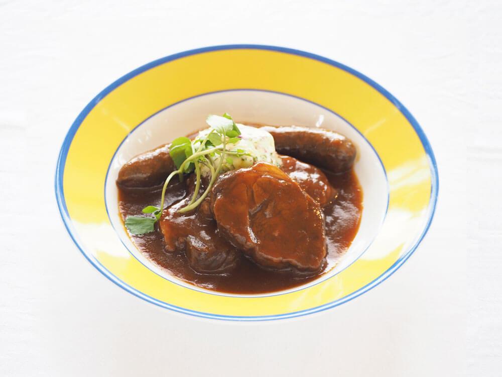 大きな塊肉とソーセージが煮込まれたビーフシチュー