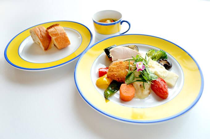 画像:イエローの縁取りが鮮やかなお揃いのお皿に盛られたメインディッシュとパン、スープ
