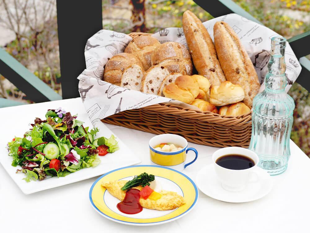 写真:真っ白なクロスが敷かれた春の庭が見えるテーブル。カゴいっぱいのパン数種類、たっぷりと盛られた野菜サラダ、季節の野菜が添えられたオムレツ、具沢山のカップスープ、コーヒー。メインの卵料理とスープはモネのイエローとブルーの縁取りが鮮やかな食器。
