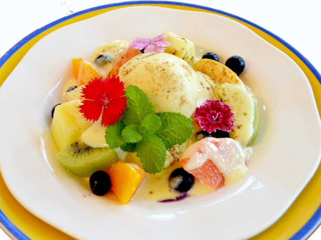 写真:バニラアイスを色とりどりのカットフルーツが囲み、カスタードソースがこんがりあぶられている。